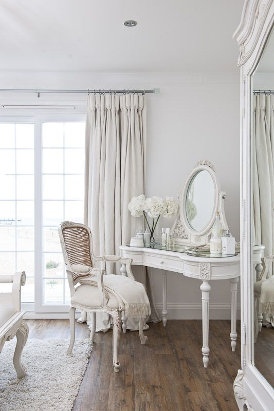 An image of a dressing room with all white walls and furniture