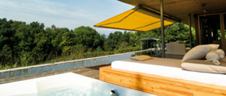 An image showing the Bobcat awning in mustard yellow and fitted over a large swimming pool